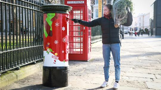 Woman posting a Christmas card in a Royal Mail postbox